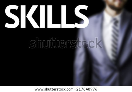 Skills written on a board with a business man on background - stock photo