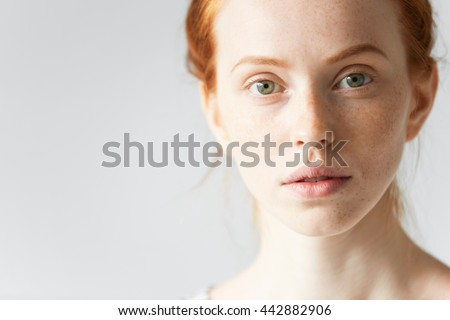 Skin care and beauty concept. Highly-detailed portrait of the face of pretty redhead female with pure healthy ideal skin with freckles looking at the camera with a faint smile and with parted lips - stock photo