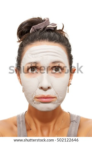 Skin care. Closeup of female face. Young woman applying clay mask. Girl taking care of her skin. Isolated. Spa and beauty treatment.