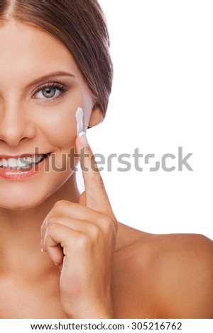 Skin care. Cropped image of young woman spreading cream on her face and smiling while standing against white background - stock photo
