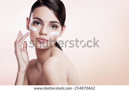 Skin care lady putting face cream / photoset of attractive brunette girl on beige background   - stock photo