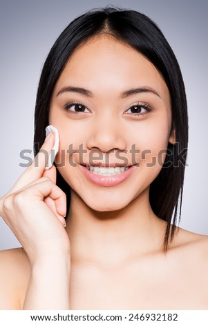 Skin care. Portrait of cheerful young and shirtless Asian woman smiling at camera and touching face with sponge while standing against grey background - stock photo