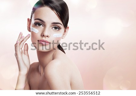 Skin care teenage girl putting face cream / photoset of attractive brunette girl on blurred beige background with bokeh   - stock photo