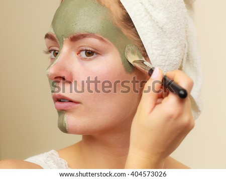 Skin care. Woman applying with brush clay mud mask to her face. Girl taking care of oily complexion. Beauty treatment. - stock photo