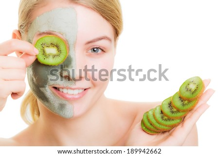 Skin care. Woman in clay mud mask on face covering eye with slice of kiwi. Girl taking care of dry complexion. Beauty treatment. - stock photo