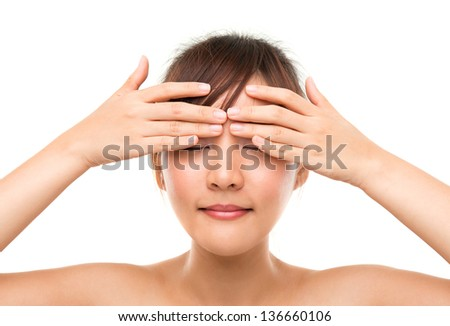 Skin care woman putting eye cream touching upper eyes. Facial beauty closeup of beautiful mixed race Asian female model isolated on white background. - stock photo