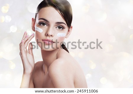 Skin care woman putting face cream / photoset of attractive brunette girl on blurred gray background with bokeh  - stock photo