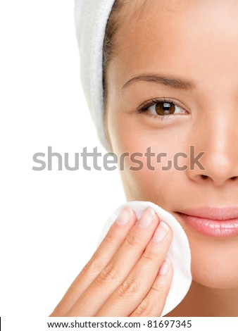 skin care woman removing face makeup with cotton swab pad - skin care concept. Facial closeup of beautiful mixed race Chinese Asian Caucasian model with perfect skin. Girl isolated on white background - stock photo