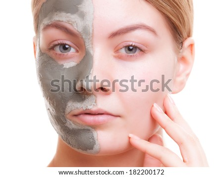 Skin care. Young woman applying clay green mud mask on her face. Girl taking care of her dry compexion. Isolated. Spa and beauty treatment. - stock photo