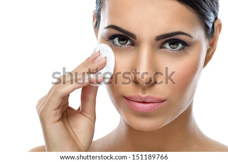 skin care, young woman cleaning her face with cotton pad - stock photo