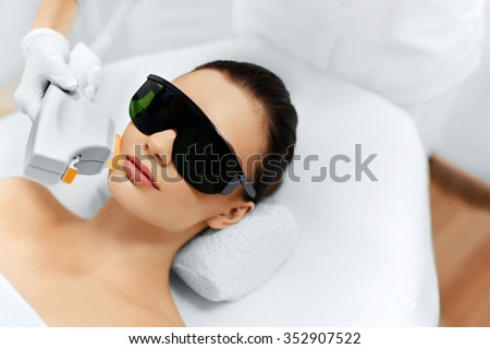 Skin Care. Young Woman Receiving Facial Beauty Treatment, Removing Pigmentation At Cosmetic Clinic. Intense Pulsed Light Therapy. IPL. Rejuvenation, Photo Facial Therapy. Anti-aging Procedures. - stock photo