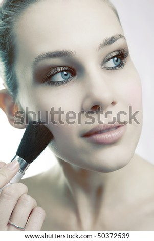 Skin cosmetics - sensual woman using brush on her face - stock photo