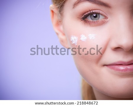 Skincare habits. Part of face of young woman with leaf as symbol of red capillary skin on violet. Girl taking care of her dry complexion applying moisturizing cream. Beauty treatment. - stock photo