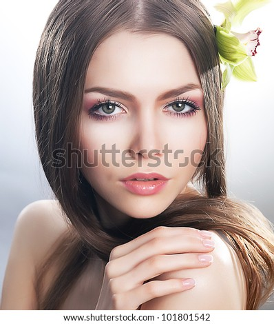Skincare of young beautiful woman face with fresh flower - orchid