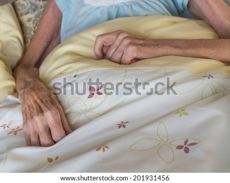 Skinny arms and hands of a very old woman lying in a bed - stock photo