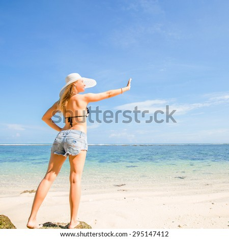 Skinny caucasian tanned woman stays on the rock against blue sky and pure ocean water, waving with her hand. Travel, vacation, holidays, paradise concept, copyspace - stock photo