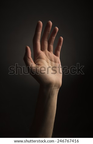 Skinny ectomorph hand reading up on black background - stock photo