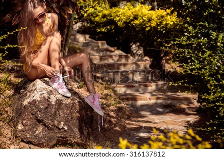 Skinny erotic young lady in a yellow swimsuit tying laces in her pink converse sneakers while sitting on a stone near steps in a tropical garden. Outdoor lifestyle picture on a sunny summer day. - stock photo