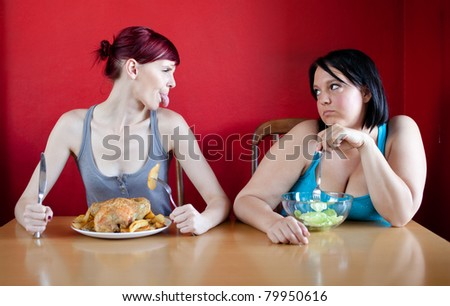 Skinny girl with a whole chicken teasing fat girl who's on a diet and eating salad. - stock photo