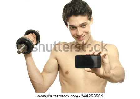Skinny man taking a selfie with his phone while training his bicep muscle. Beautiful teenager lifting a dumbbell and taking a photo for facebook.Anorexic young man training to become stronger - stock photo