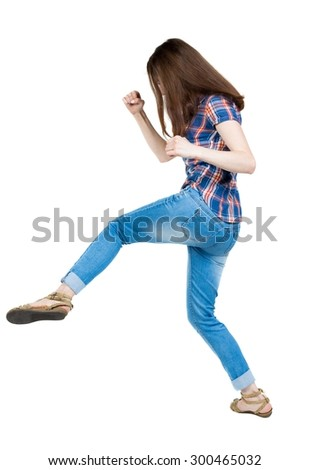 skinny woman funny fights waving his arms and legs. Isolated over white background. A young girl in a checkered blue with red stripes make kick-boxing punch. - stock photo