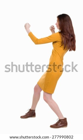 skinny woman funny fights waving his arms and legs. Rear view people collection.  backside view of person.  Isolated over white background. Girl dress in mustard in a fight. - stock photo