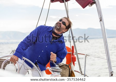 Skipper looking up to sail, controlling the rope , during the sailing - stock photo