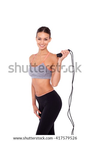Skipping rope is her way to fitness. Portrait of an attractive young sporty woman holding a skipping rope while standing over white isolated background. - stock photo