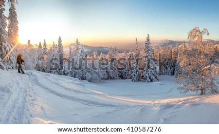 skitour skier in the woods with a backpack hiking in winter - stock photo