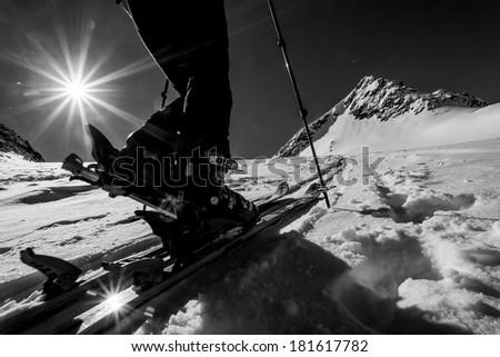 Skitouring - detail of a ski binding during winter mountain ascent - stock photo