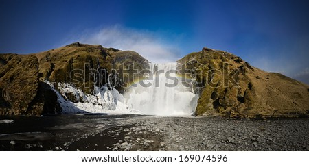 Skogafoss, Iceland, famous waterfall with rainbow covered with ice - stock photo