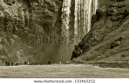 Skogafoss waterfall and rainbow in Iceland (stylized retro) - stock photo