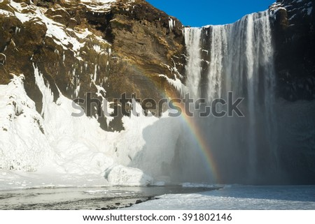 Skogafoss waterfall with snow and rainbow at winter, Iceland