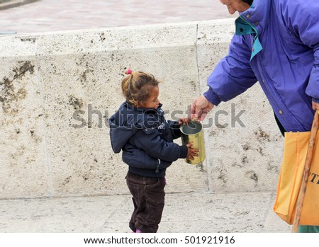 SKOPJE, MACEDONIA - OCTOBER 18,2016:Older woman gives money to cute beggar girl downtown of Skopje,capital of Macedonia