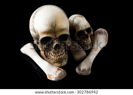 skull and bones on black background - stock photo