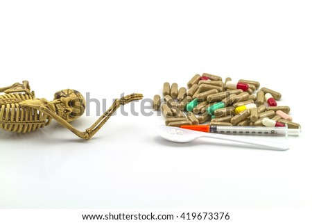 Skull and drugs with insulin syringe. Next to them are a spoon with white powder, which is similar to heroin on white background,touch - up in still life concept. - stock photo