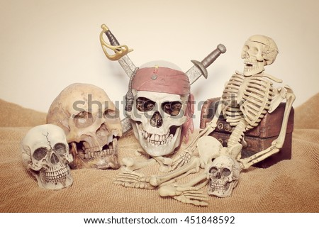 skull and swords pirate of the Caribbean & human skeleton with Old wooden chest on the brown fabric. - stock photo