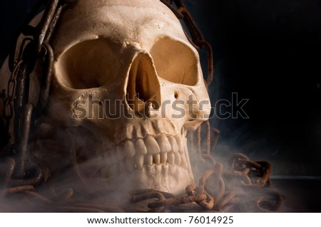 Skull in abstract smoke with chains on it - stock photo