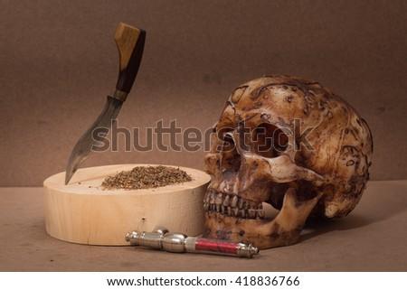 skull with marijuana drug still-lift concept dark tone - stock photo