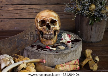 Skull with millipede in eye socket and knife be stained with blood on cutting block /still life style