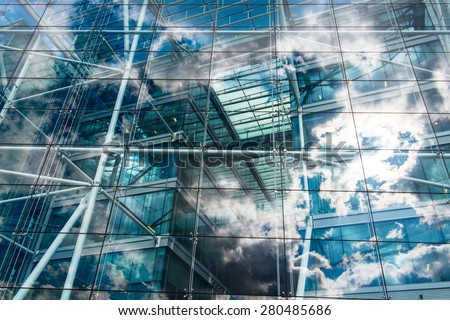 Sky and clouds reflected in the windows of an ecological and sustainable building. - stock photo