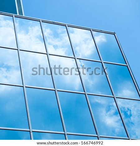 Sky and clouds reflected in windows of modern office building. - stock photo