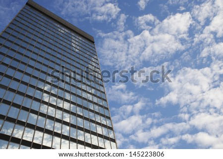 Sky and clouds reflecting in skyscraper windows low angle view - stock photo