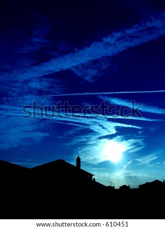 sky and silhouetted houses - stock photo