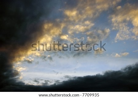 Sky at Dusk with Sun setting behind clouds - stock photo