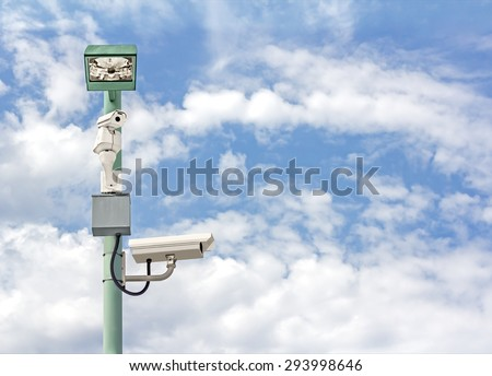 Sky high security camera and light. CCTV surveillance cameras looking in different directions. Blue sky and clouds background.  - stock photo