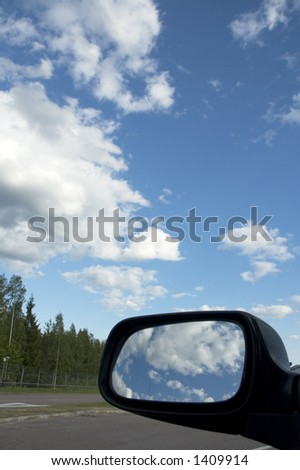 sky reflecting in rear view mirror - stock photo
