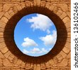 Sky view through a round hole of the old stone wall - stock photo