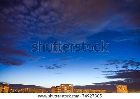 sky with clouds over city after sunset - stock photo