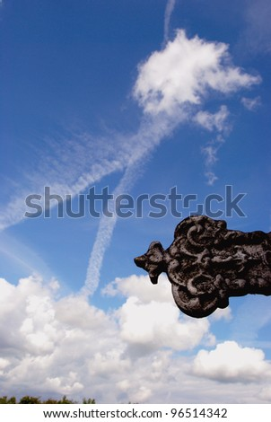 Sky with many clouds and religion item in front of it. - stock photo